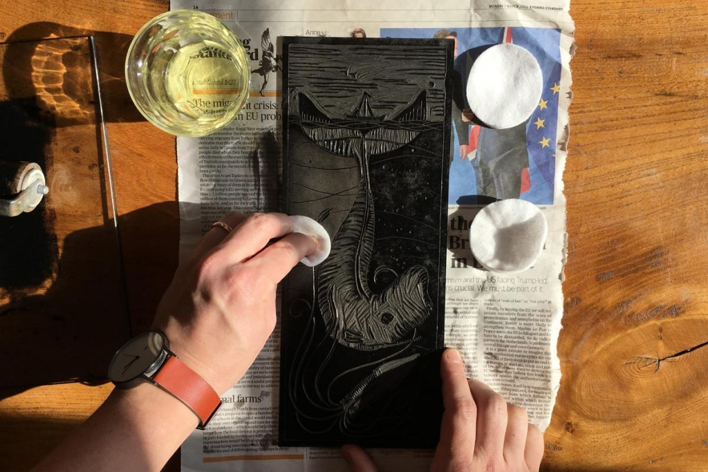 Cleaning a linocut with vegetable oil and a cotton wool pad, you can see the ink wiped away on the pad