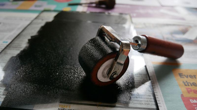 lino printing - applying linocut ink. ink on roller